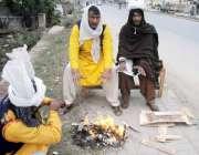 راولپنڈی: شدید سردی کے باعث ڈھولچی سڑک کنارے آگ تاپ رہے ہیں۔