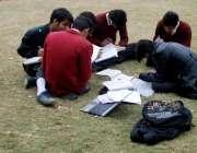 راولپنڈی: طلبہ مقامی پار میں بیٹھے ہوم ورک کر رہے ہیں۔