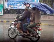 لاہور: شہر میں ہونیوالی بارش کے دوران موٹر سائیکل سوار شہری اپنی منزل ..