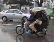 لاہور: موٹر سائیکل سوار بارش سے بچنے کے لیے سروں پر پلاسٹک رکھے جا رہے ..