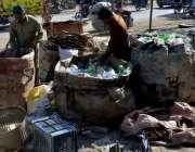 لاہور: خانہ بدوش افراد پلاسٹک کی بوتلیں بیچنے کے لیے اکٹھے کر رہے ہیں۔
