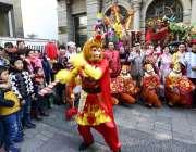 چائنہ: ایک شخص جشن بہاراں کے سلسلے میں بندر نما لباس پہنے لوگوں کو محضوض ..