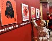 چائنہ: ایک بچی تصویروں کی نمائش دیکھنے میں مصروف ہے۔