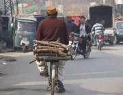لاہور: ایک سائیکل سوار گیس کی لوڈ شیڈنگ کے باعث گھر کا چولہا جلانے کے ..