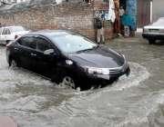 راولپنڈی:تیز بارش کے بعد جمع شدہ پانی سے ایک گاڑی گزر رہی ہے۔