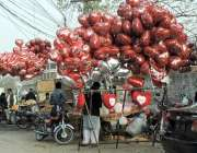 لاہور: ایک محنت کش ویلنٹائن ڈے کی مناسبت سے دل نما غبارے فروخت کر رہا ..
