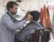 لاہور: شملہ پہاڑی چوک میں فٹ پاتھ پر لگائی گئی دوکان پر ایک حجام بال ..