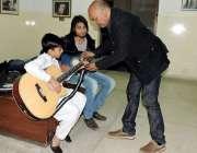 لاہور: صفدارتی ایواڈ یافتہ سجاد طافو ایک بچے کو گٹار بجانا سکھا رہے ..