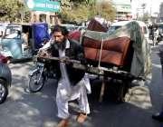 لاہور: ایک محنت کش ہتھ ریڑھی پر بھاری سامان رکھے پریس کلب کے سامنے سے ..