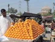 لاہور: کینال روڈ پر ایک پھل فروش گاہکوں کو متوجہ کرنے کے لیے کینو ریڑھی ..