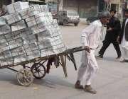 لاہور: ایک محنت کش ہتھ ریڑھی پر بھاری سامان رکھے جا رہا ہے۔