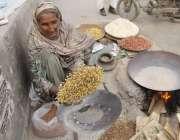 لاہور: ایک بھٹیارن سڑک کنارے دکان سجائے بیٹھی ہے۔