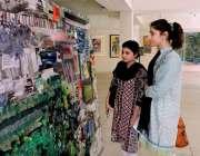 لاہور: لڑکیاں الحمراء میں جاری پینٹنگ کی نمائش دیکھ رہی ہیں۔