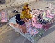 کراچی: ایک عورت سڑک کنارے اپنے بچے کے ہمراہ کرسیاں فروخت کے لیے سجا ..