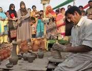 لاہور: جیلانی پارک میں جاری جشن بہاراں فیسٹیول میں شہری کمہار کو مٹی ..