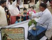 لاہور: جیلانی پارک میں جاری جشن بہاراں فیسٹیول میں ایک خاتون طوطے سے ..
