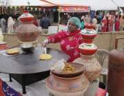 لاہور: جیلانی پارک میں جاری جشن بہاراں فیسٹیول میں ایک خاتون مکئی کی ..