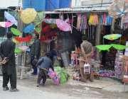 کوئٹہ: لیاقت بازار میں لوگ بارش سے بچنے کے لیے ایک دوکان سے چھتریاں ..