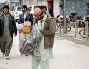 کوئٹہ: عدالت روڈ پر ایک شخص ٹوپیاں فروخت کرنے کے لیے بازار کی جانب جا ..