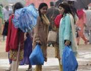 لاہور: جیلانی پارک میں دو خواتین نے بارش سے بچنے کے لیے چھتری تان رکھی ..
