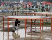 لاہور: جیلانی پارک میں جاری جشن بہاراں فیسٹیول میں ایک شخص بارش سے بچنے ..