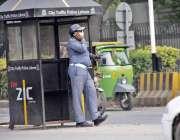 لاہور: چیئرنگ کراس چوک میں ڈیوٹی پر مامور ٹریفک وارڈن موبائل فون پر ..
