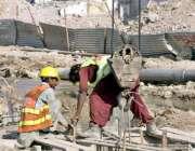 لاہور: دو مزدور میٹر ٹرین منصوبے پر کام میں مصروف ہیں۔
