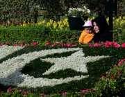 لاہور: ریس کورس پارک میں ایک خاتون پھولوں سے بنائے گئے قومی پرچم کے ..