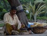 لاہور: ایک محنت کش باغ جناح میں پاپڑ بیچ رہا ہے۔