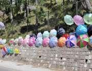 راولپنڈی: مری کے راستے میں ایک محنت کش نے سڑک کنارے چھتریاں سجا رکھی ..