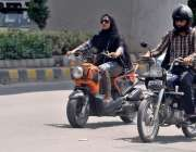 راولپنڈی: ایک خاتون سکوٹی چلاتے ہوئے مری روڈ سے گزر رہی ہے۔
