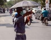 لاہور: مال روڈ پر ایک ٹریفک وارڈن گرمی اور دھوپ کے شدت سے بچنے کے لیے ..