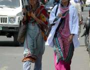 لاہور: دھوپ سے بچنے کے لیے خواتین چھتری لیے فیروزپور روڈ سے گزر رہی ..