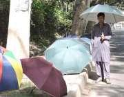 لاہور: چھتریاں فروخت کرنے کے لیے سڑک کنارے کھڑے ایک محنت کش نے دھوپ ..