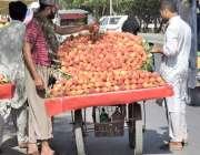 لاہور: ایک محنت کش گاہکوں کو متوجہ کرنے کے لیے آڑو ریڑھی پر سجا رہا ہے۔
