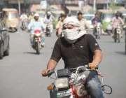 لاہور: ایک موٹر سائیکل سوار شہری دوپہر کے وقت شدید دھوپ سے بچنے کے لیے ..