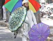 لاہور: ایک محنت کش چھتریاں فروخت کرنے کے لیے گاہکوں کا انتظار کر رہا ..