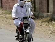 لاہور: ایک معذور شخص موٹر سائیکل پر اپنی منزل کی طرف گامزن ہے۔