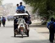 لاہور: سکول کے بچے خطرناک طریقے سے رکشہ کی چھت پر سفر کر رہے ہیں جو کسی ..
