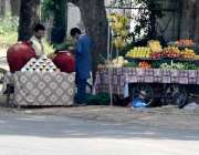 راولپنڈی: ریڑھی بان نے روڈ کنارے ریڑھی پر پھل سجائے ہوئے ہیں جبکہ ایک ..