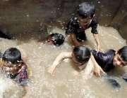 حیدر آباد: گرمی کی شدت کم کرنے کے لیے بچے ایک تالاب میں نہا رہے ہیں۔