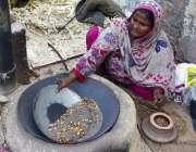 لاہور: ایک محنت کش خاتون فروخت کے لیے بھٹی پر چنے تیار کر رہی ہے۔