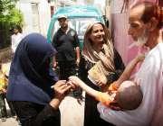 کراچی: پولیو ورکر سخت سیکیورٹی میں ایک بچے کو پولیو قطرے پلانے کے بعد ..