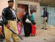 کراچی: لیڈی ہیلتھ ورکر پولیس کی نگرانی میں بچوں کو پولیوں کے قطرے پلارہی ..
