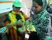 کراچی: پولیو مہم کے دوران لیڈی ہیلتھ ورکر ایک بچے کو پولیو کے قطرے پلا ..