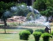 راولپنڈی: محنت کش دوپہر کے وقت نواز شریف پارک میں پودوں کا پانی لگا ..