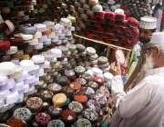 کراچی: رمضان المبارک کی آمد کے موقع پر شہری سڑک کنارے سجی دکان سے ٹوپیاں ..
