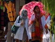 اسلام آباد: دھوپ کی شدت سے بچنے کے لیے خواتین چھتری تانے اپنی منزل کی ..