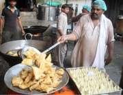 لاہور: رمضان المبارک کی پہلی افطاری کے لیے حلوائی سموسے تیار کر رہا ..
