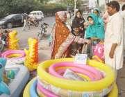 لاہور: خواتین سڑک کنارے فروخت کے لیے رکھے چھوٹے سوئمنگ پول خرید رہی ..